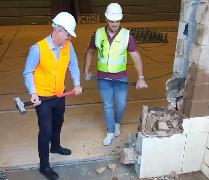 Sport Minister Stirling Hinchliffe and discus athlete Matt Denny get started on demolition work at QSAC's indoor court.